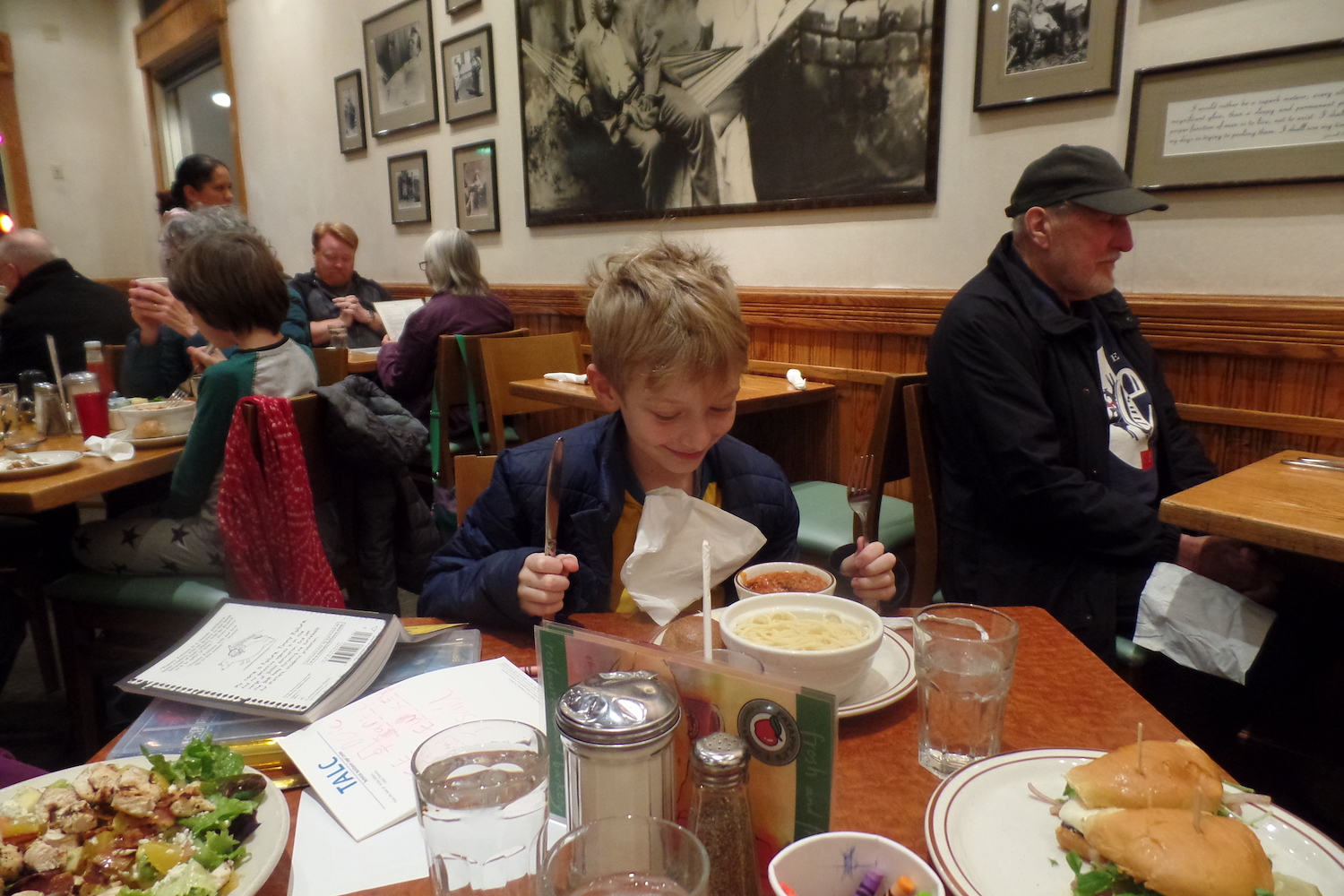 An 8-year-old boy sits with a napkin as a bib holding a fork and knife in his hands in front of a plate bowl of plain spaghetti noodles and a side of sauce at Fatapple's in Berkeley.