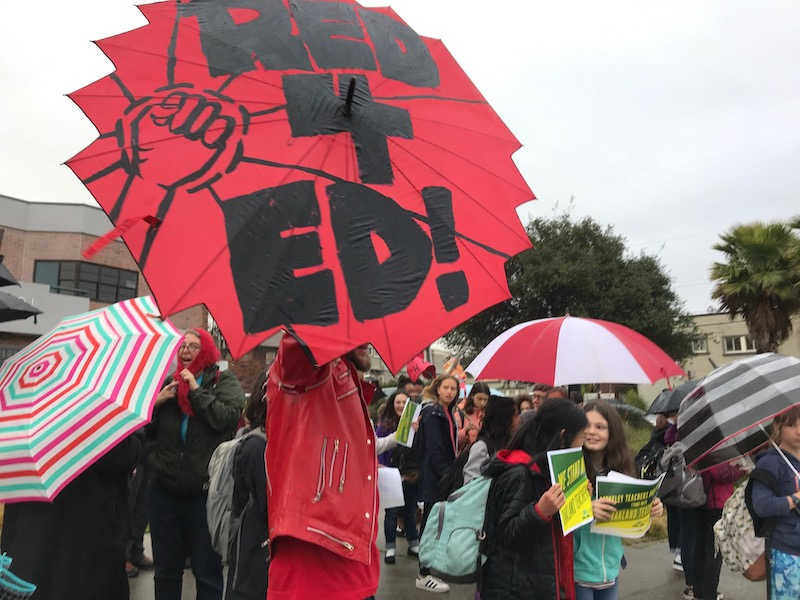 """Teacher dressed all in red holds red umbrella that says, """"Red 4 Ed!"""" Other people rally behind him."""