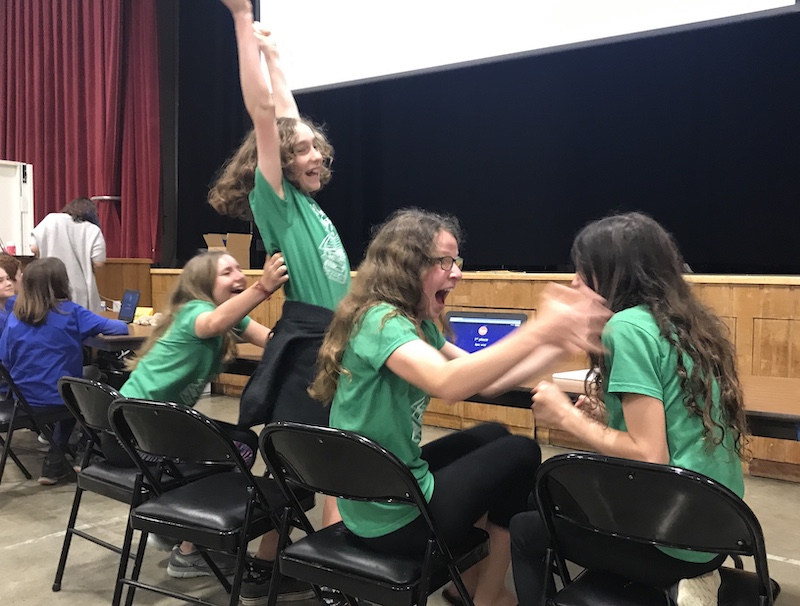 Four students in green shirts jump for young with shocked faces.