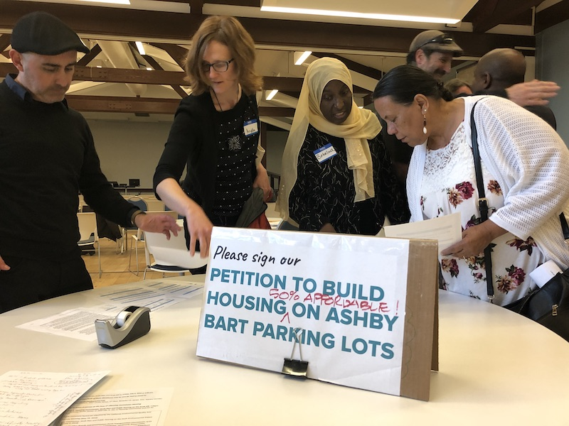 """In the foreground, a sign on a table says """"Please sign our petition to build housing on Ashby BART parking lots."""" Four people stand behind the table peering at the materials."""