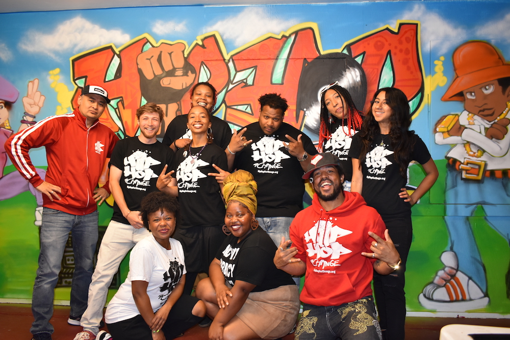 Hip Hop For Change Staff poses in front of their mural at their HQ in Oakland