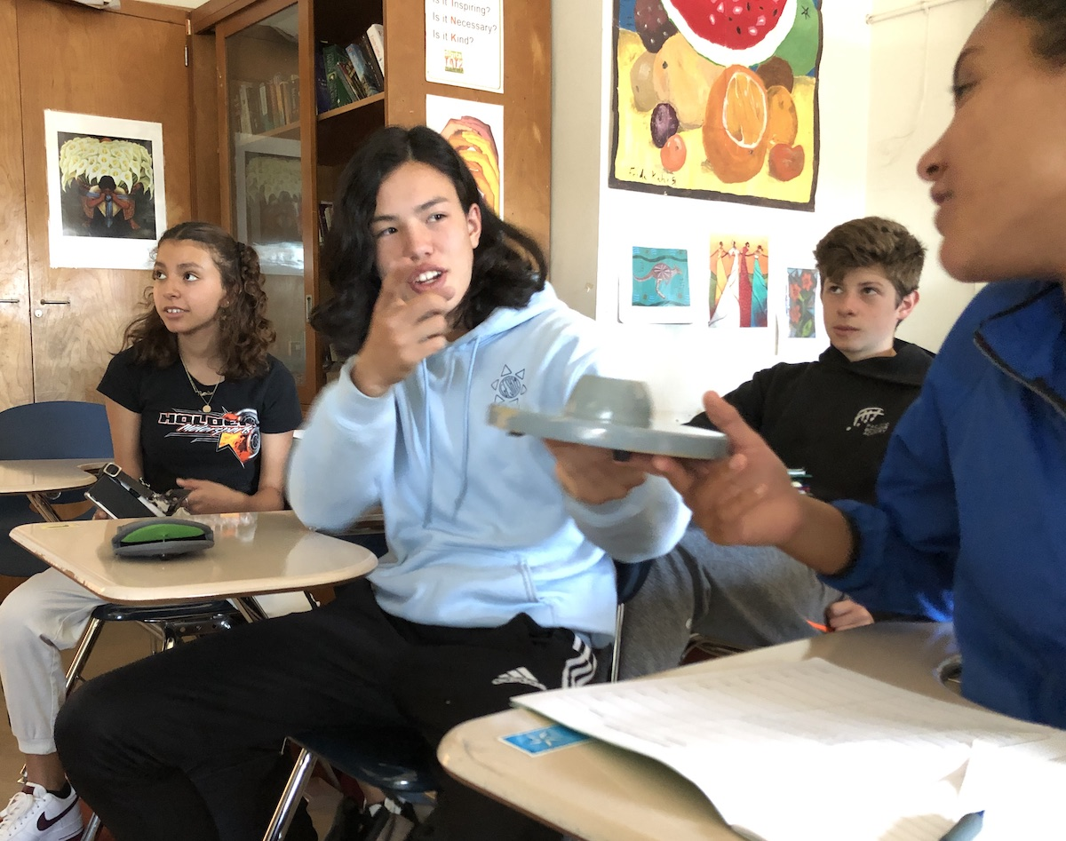 Teenagers sit at desks. One is passing a grey disk to another.