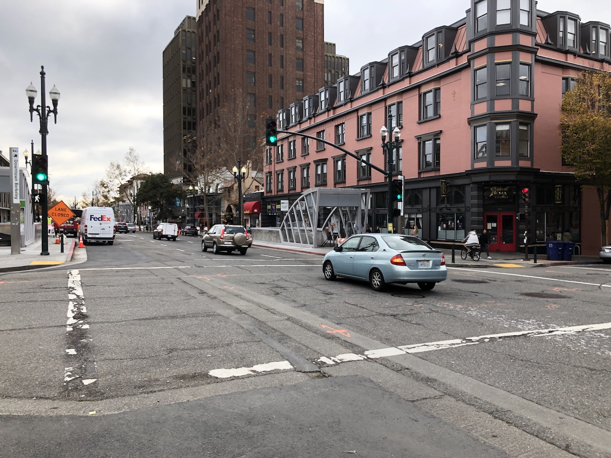 cars drive on a one-way street with large buildings in the background
