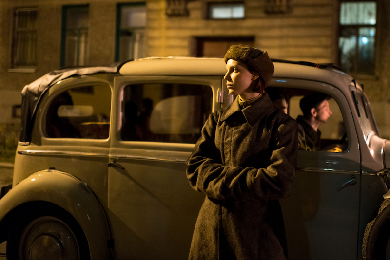 woman dressed in military clothing leans against a car