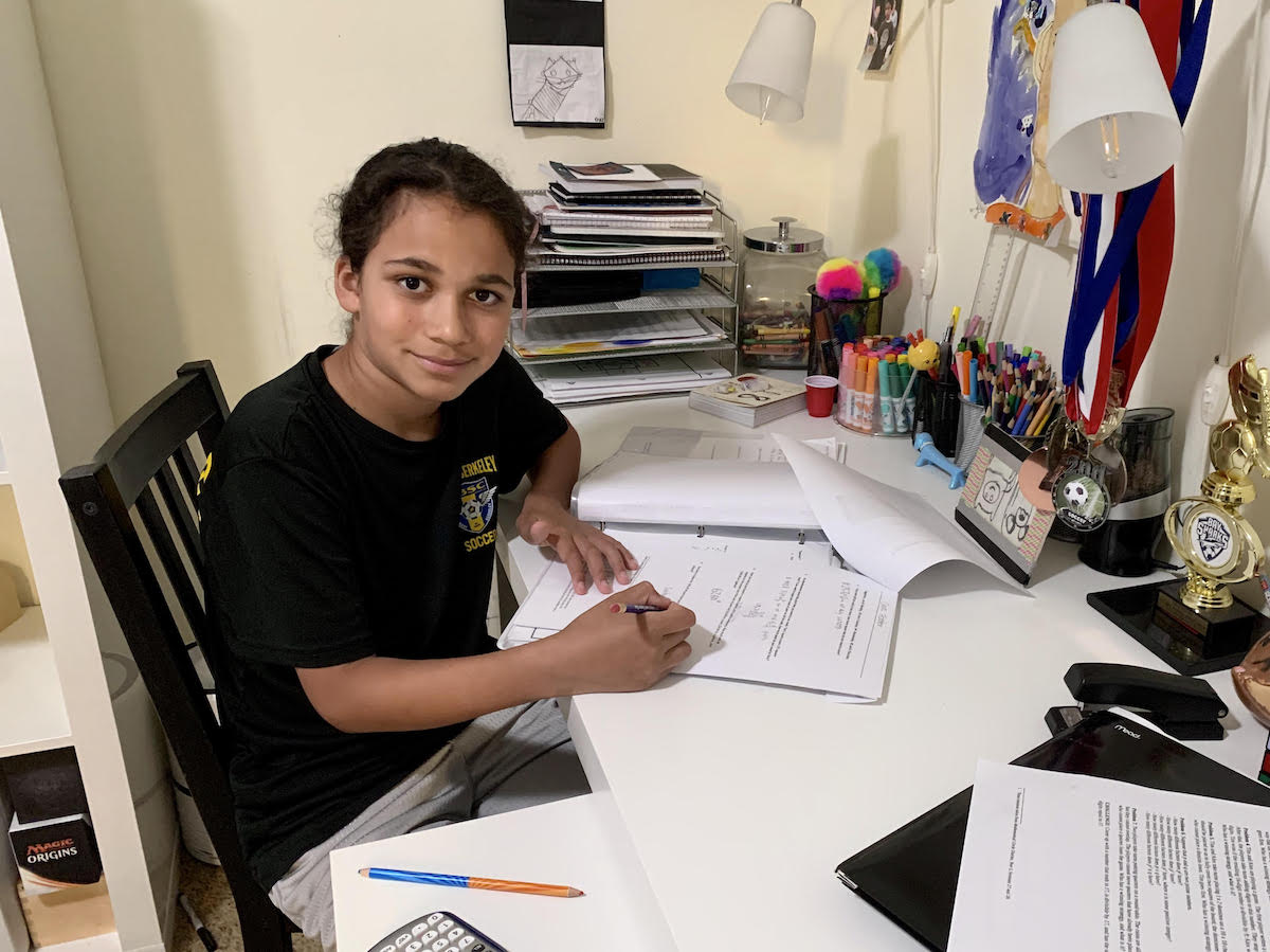 a boy sits at a messy desk working on something. Smiles at the camera