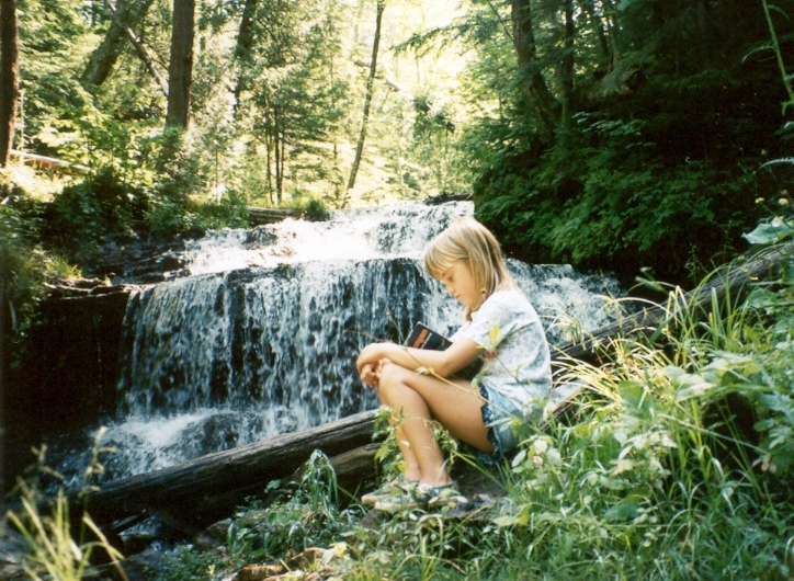 young girl reading in front of waterfall