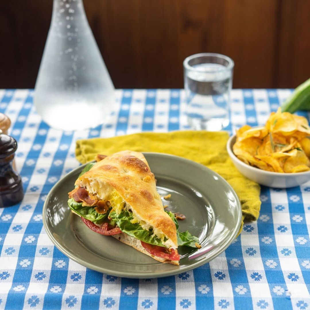 The Chez Panisse BLT sits on a plate with a plate of potato chips and a glas of water and carafe in the background on a blue and white checker tablecloth. Photo: Chez Panisse