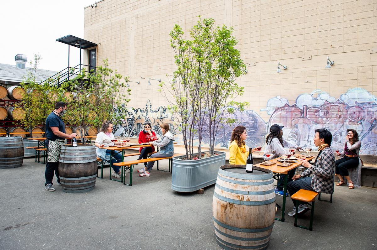 Groups of people at socially distanced tables enjoy outdoor wine tastings at Donkey & Goat in Berkeley. Photo: Sari Blum