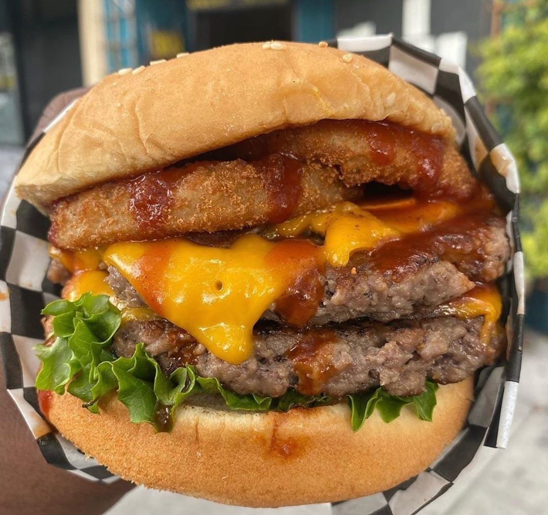 A hand holds up a burger from Malibu's Burger, made with two meatless patties, onion rings, vegan cheese, lettuce.