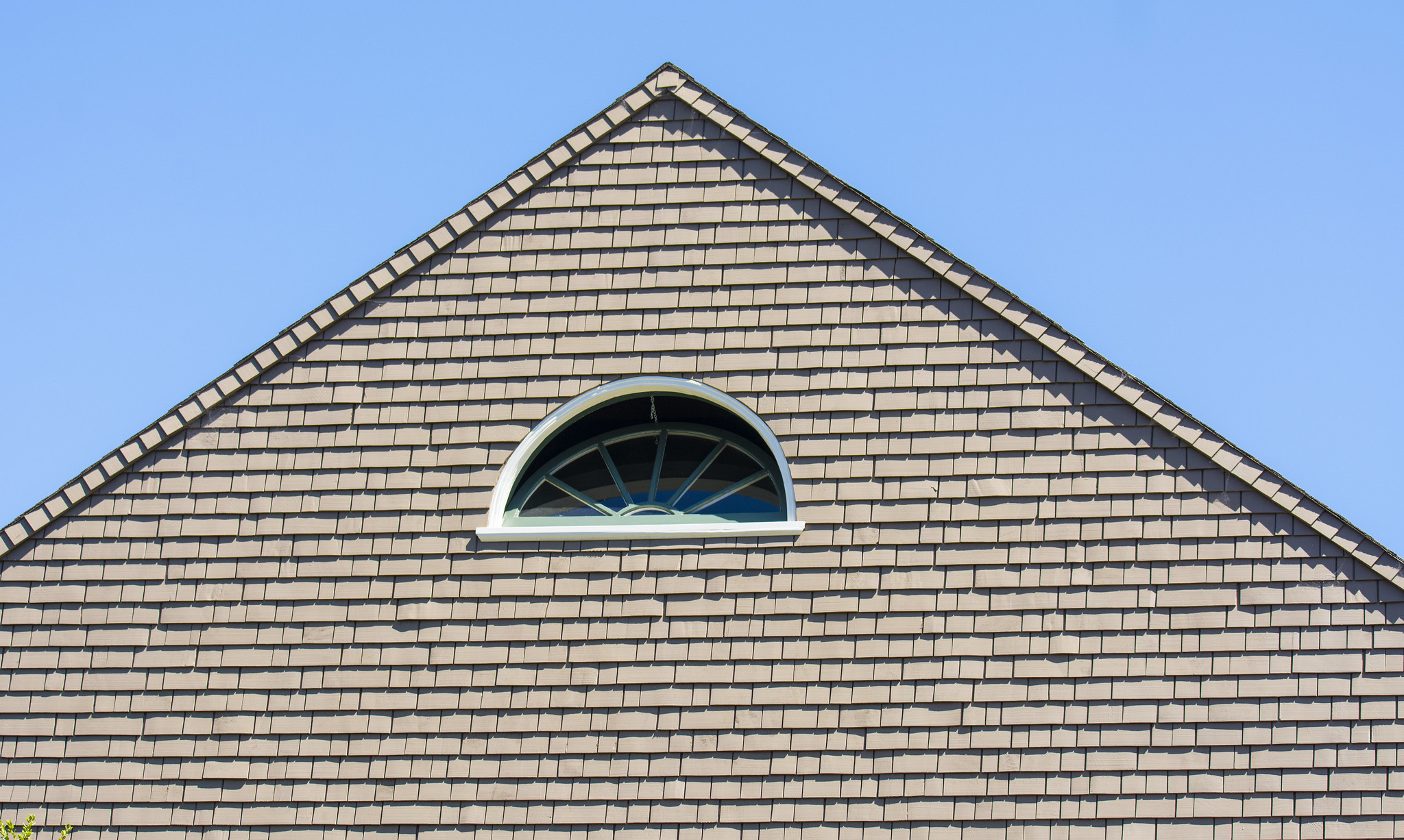 Peaked facade of a shingle house with a semicircular window