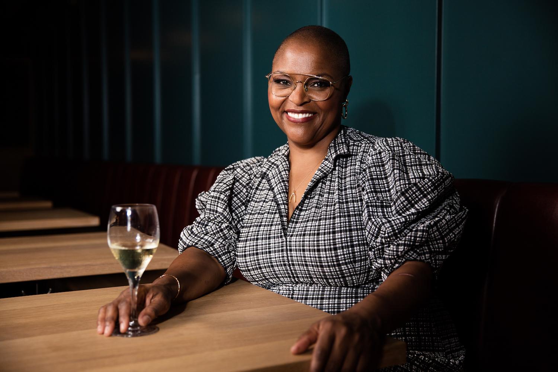 Chef Tanya Holland sits at a booth with a glass of wine at Brown Sugar Kitchen in Oakland. Photo: Smeeta Mahanti