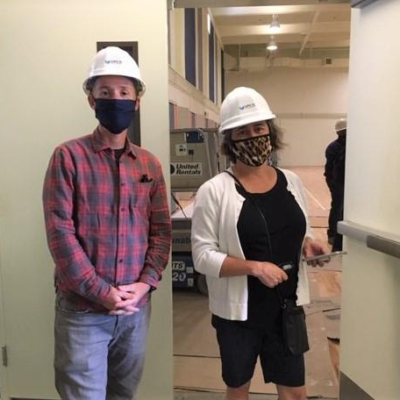 Two people standing side-by-side wearing masks and hardhats