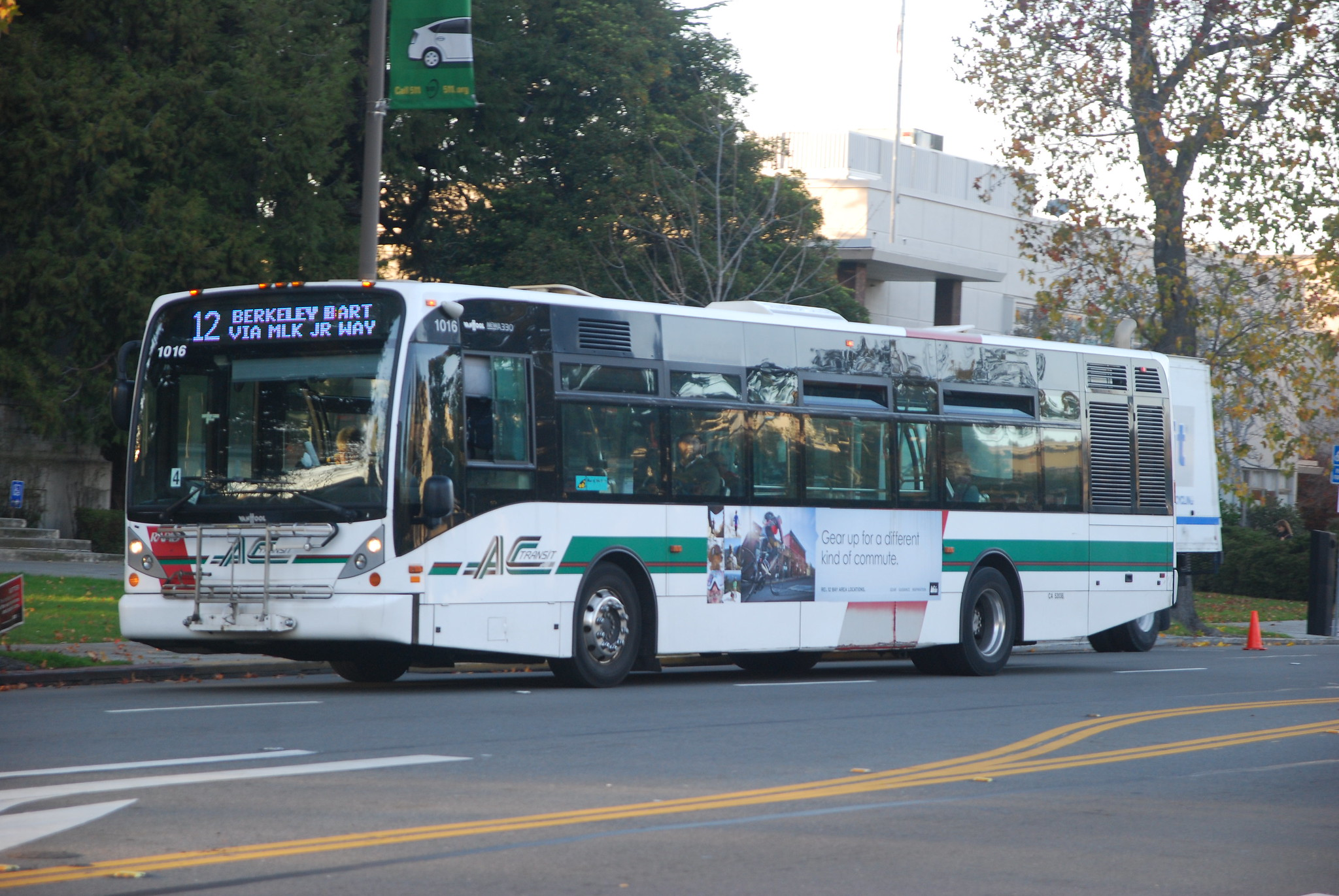 "a green and white bus, AC Transit line 12, labeled ""Berkeley BART via MLK Jr Way"""