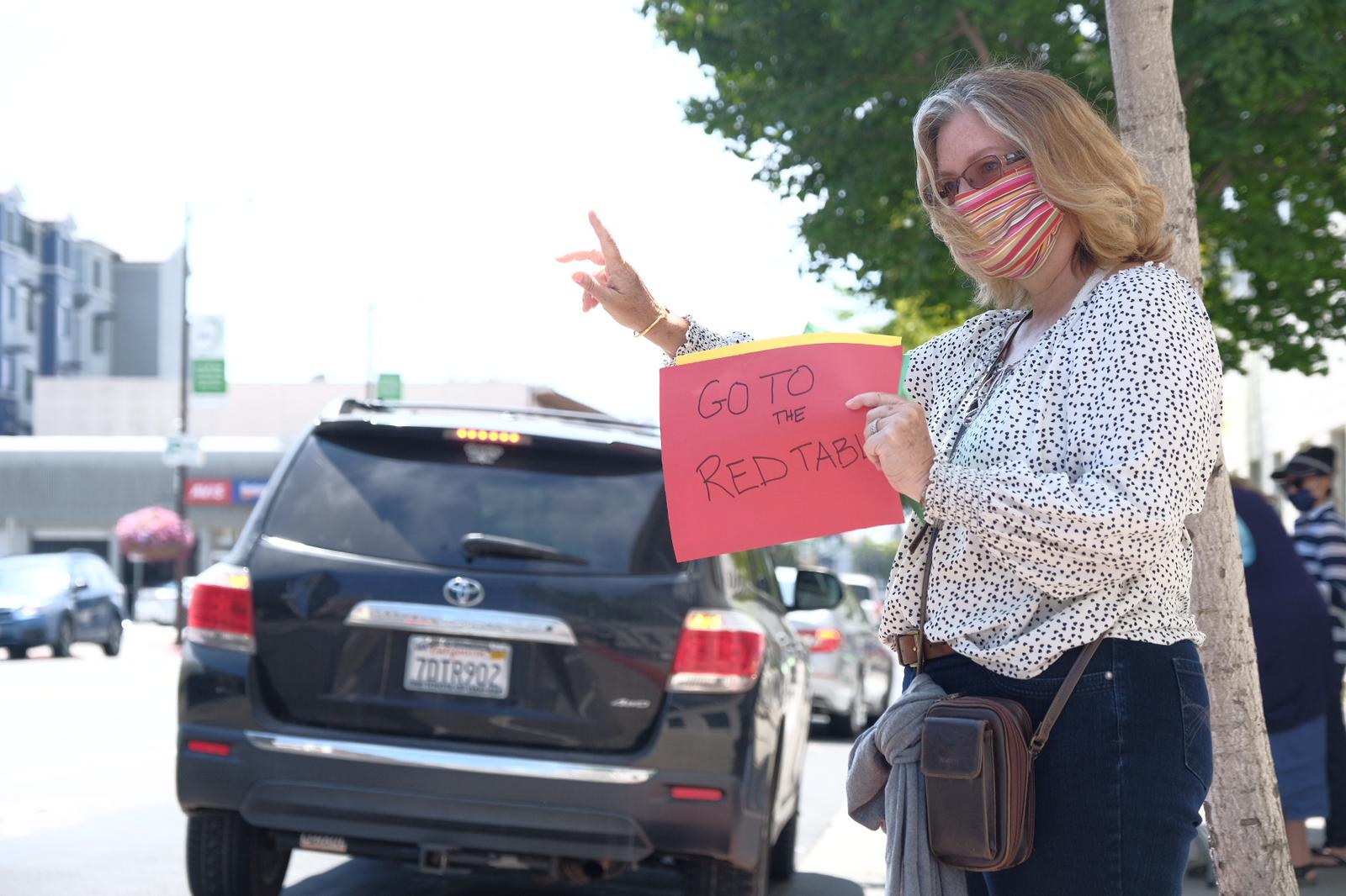 "A volunteer holds up a sign that says ""Go to red table"" during drive-through registration"