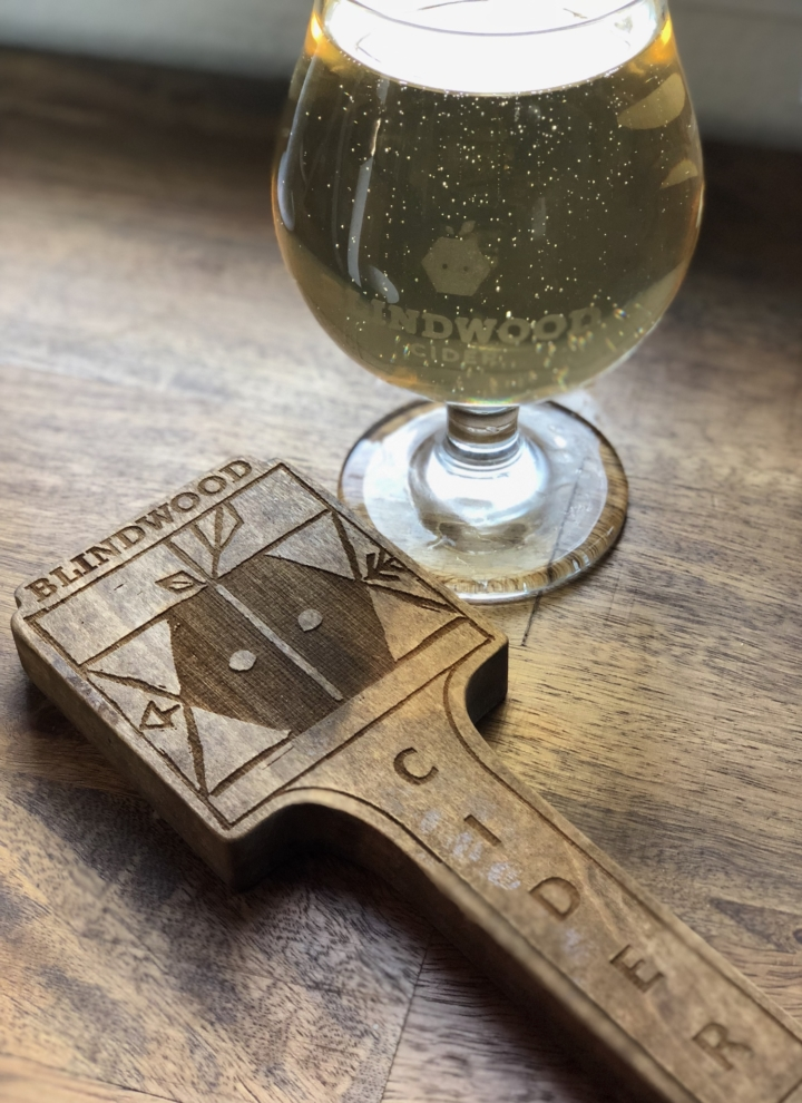 A glass of Blindwood cider and a Blindwood tap handle sit on a table.