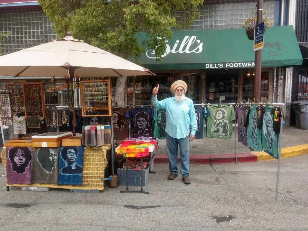 a man stands in front of his booth selling goods on Telegraph Avenue