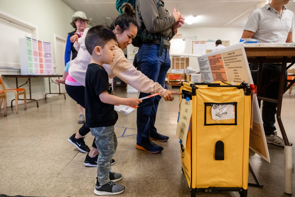 Voter Jenny Vallecer assists son Liam in depositing her ballot at St. Ambrose Church in Westbrae, Northwest Berkeley. Photo: Kelly Sullivan