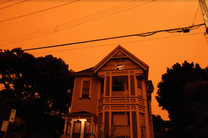 a victorian house in front of orange skies